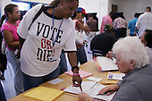Miami-Dade County, Florida.USA.November 2, 2004..Voters line up with observers and lawyers from both sides watching over the voters and pollsters...A voters wears the tee shirt with the rapers P.Diddy sloggen.