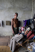 U Hla Tin (68) is paralysed from the left side of the body. As the cylone nargis hit, the first thing he could think of was his ailing wife. His wife, Daw Sein (60) is ill and with no options left, U Hla Tin carried her on his back and brought her to the shopping complex. Mr. Tin hasn't been back to see his hut but doesn't believe his neighbours when they say that his hut is all destroyed during the cyclone Nargis. Here he poses with his ill wife, Daw Sein...Refugees from the 7th ward, Hlaing Thayar township take shelter in the Swethanlwin building shopping complex which is  under construction and has acted as a small refugee centre outside of capital Yangoon, Myanmar.