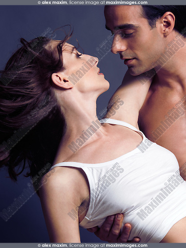 Artistic closeup portrait of a sexy young couple faces about to kiss