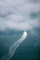 aerial view above San Francisco Vallejo ferry disappearing into the fog crossing San Francisco bay..