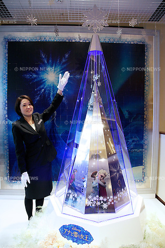 """A staff poses for the cameras next to the """"Disney Platinum Christmas Tree"""" made of platinum at Ginza Tanaka jewelry store in Ginza, Tokyo on November 19, 2014. The large version of the Disney tree is made of platinum and decorated with the characters of the worldwide hit movie Frozen. It has a 2.6 meter height and 31kg weight and it costs approximately 2.6 million USD. The small silver version costs 4000 USD and both are on sale from November 19.  (Photo by Rodrigo Reyes Marin/AFLO)"""