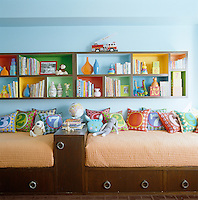 In a child's bedroom matching twin beds are set against one wall with custom-made bookshelves above