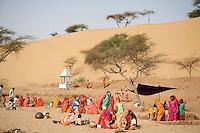 Women preparing and working on Waterholes for the short rainy season in the Thar Desert near Jaiselmer, Rajasthan,T h e   T h a r   D e s e r t   a l s o   k n o w n   a s   t h e   G r e a t   I n d i a n   D e s e r t ,   i s   a   l a r g e ,   a r i d   r e g i o n   i n   t h e   n o r t h w e s t e r n   p a r t   o f   t h e   I n d i a n   s u b c o n t i n e n t .   W i t h   a n   a r e a   o f   m o r e   t h a n   2 0 0 , 0 0 0   s q .   k m  ( 7 7 , 0 0 0   s q .   m i . )   i t   i s   w o r l d ' s   1 8 t h   l a r g e s t   d e s e r t .   I t   l i e s   m o s t l y   i n   t h e   I n d i a n   s t a t e   o f   R a j a s t h a n ,   a n d   e x t e n d s   i n t o   t h e   s o u t h e r n   p o r t i o n   o f   H a r y a n a   a n d   P u n j a b   s t a t e s   a n d   i n t o   n o r t h e r n   G u j a r a t   s t a t e .   I n   P a k i s t a n ,   t h e   d e s e r t   c o v e r s   e a s t e r n   S i n d   p r o v i n c e   a n d   t h e   s o u t h e a s t e r n   p o r t i o n   o f   P a k i s t a n ' s   P u n j a b   p r o v i n c e .   T h e   C h o l i s t a n   D e s e r t   a d j o i n s   t h e   T h a r   d e s e r t   s p r e a d i n g   i n t o   P a k i s t a n in   the P u n j a b   p r o v i n c e .