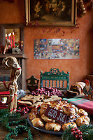 Detail of a Swedish Christmas table with plates of traditional bread and cookies decorated with berries, foliage and straw figures