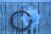Detail of a round metal handle with a blue star-shaped base on a wooden window shutter in the medina or old town of Chefchaouen in the Rif mountains of North West Morocco. Chefchaouen was founded in 1471 by Moulay Ali Ben Moussa Ben Rashid El Alami to house the muslims expelled from Andalusia. It is famous for its blue painted houses, originated by the Jewish community, and is listed by UNESCO under the Intangible Cultural Heritage of Humanity. Picture by Manuel Cohen