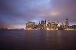 The lights of the downtown New York City skyline reflect off the East River at sunset on a cloudy day.  The New York City harbor is to the left. The streak in the sky is a NYC police helicoptor flying security over the World Trade Center Memorial site.