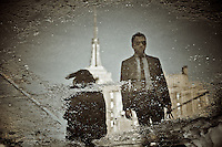 Reflection in a puddle of a guy with glasses passing by the Empire State Building in New York