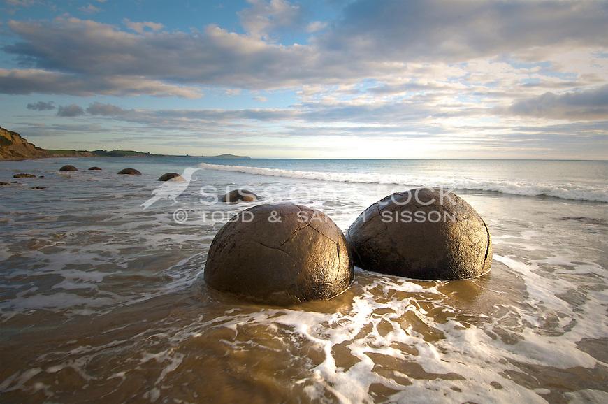 Moeraki Boulders image | round rocks in sea | golden sun | waves around boulders | Coastal Otago New Zealand