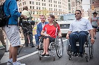 Kristina Rhoades, spokesperson for MV-1 handicapped accessible vehicle from Mobility Ventures is interviewed during the First Disability Pride Parade in New York on Sunday, July 12, 2015.  The ADA ensured accessibility to the disabled and removed barriers to employment, transportation, public accommodations, public services and telecommunications. (© Richard B. Levine)