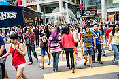 Pedestrians cross the street outside the Pavilion, a high end shopping mall in Kuala Lumpur, Malaysia.