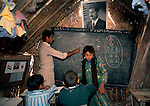 Marsh Arabs. Southern Iraq. Circa 1985. Marsh Arab children in school building. Traditional reed constructed building. Portrait of Saddam Hussein hanging from wall.