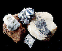 TRANSITION METAL ORES with rare earths (clockwise) Thorianite (brown) -Thorium uranium oxide (Th,U)O2; Monazite (white) a rare earth phosphate; Rutile -Titanium oxide; Columbite-Tantalite group (gray stripe on white) -Oxides of rare earths (Fe, Mn)(Nb,Ta)2O6; Cobaltite -Cobalt arsenic sulfide.