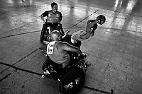 Charly Neme, a Colombian disabled athlete, prepares to pass the ball during a wheelchair rugby training match at the indoor sporting arena Coliseo in Bogota, Colombia, 29 January 2013. Wheelchair rugby, a full-contact team sport, was developed in Canada in 1977 under the name murderball. The game is played only by athletes with some form of disability in both the upper and lower limbs (quadriplegics). Attempting to score by carrying the ball across the goal line, four players from each team roughly crash into each other in specially designed armored wheelchairs. Although the team from Bogota is supported by a foundation (gear), quad rugby players, mostly coming from the remote, socially deprived neighbourhoods, often can not attend a training due to lack of funds for transportation. However, they still dream of representing Colombia at Rio 2016 Paralympic Games.