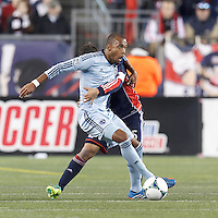 Tightly defended Sporting Kansas City forward Teal Bunbury (9) controls the ball. In the first game of two-game aggregate total goals Major League Soccer (MLS) Eastern Conference Semifinal series, New England Revolution (dark blue) vs Sporting Kansas City (light blue), 2-1, at Gillette Stadium on November 2, 2013.