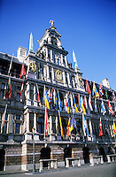 The city hall of Antwerp, Belgium is covered with flags.