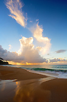 At sunset, the clouds in the sky mirrors the outline of the receding surf at Secrets Beach on the north shore of Kaua'i.