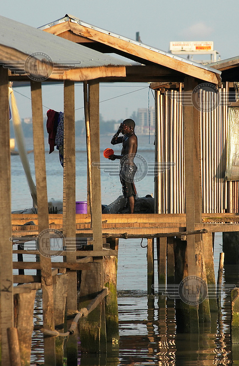 A man bathes using a bucket outside his house built on stilts above the water.