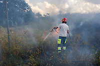 Roma 28 Giugno 2013<br /> Incendio di sterpaglie in via Casilina al civico 900, ex campo rom. Un addetto della squadra antincendio della Protezione Civile durante le operazioni di spegnimento dell' incendio.