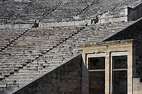 EPIDAURUS, GREECE - APRIL 15 : A detail of the Cavea of the Theatre, on April 15, 2007 in Epidaurus, Greece. The Theatre, designed by Polykleitos the Younger, was built in the late 4th century BC and extended in the Hellenistic period. It was rediscovered in 1881 and significantly restored in the 1950s.  It has the three main features of a Greek theatre: the orchestra; the skene and the cavea, a raked semi-circular auditorium with radiating diazomas. The theatre is renowned for its accoustics thanks to the symmetry of the cavea, seen here in the early morning light, with the entrance to one of the two paradoi, or corridors, which gave the actors access to the stage. (Photo by Manuel Cohen)