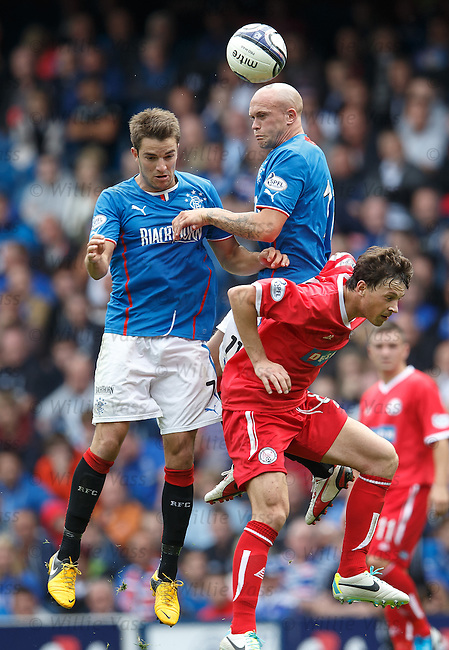 Andy Little and Nicky Law of Rangers challenge Brechin City's Stuart Henderson in the air