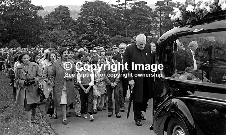 Roman Catholic priest Rev Padraig Murphy, head bowed, follows the funeral of the Good Samaritan, Samuel Llewellyn, a 28 year old Protestant from the Shankill district of Belfast, N Ireland, who was murdered by the Provisional IRA. Mr Llewellyn was making his third trip with a load of hardboard for repairs to the Clonard area following a car bomb explosion when he was shot dead. Such was the outrage that many Lower Falls residents placed sympathy notices in local newspapers. Obviously Father Murphy, also felt it his duty to attend the funeral. 197508190604d..Copyright Image from Victor Patterson, 54 Dorchester Park, Belfast, United Kingdom, UK...For my Terms and Conditions of Use go to http://www.victorpatterson.com/Victor_Patterson/Terms_%26_Conditions.html