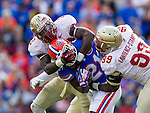 FSU defenders Telvin Smith (22) and Nile Lawrence-Staple wrap up Gator running back Kelvin Taylor (21) in the 2nd half of the #2 ranked Florida State Seminoles 37-7 victory over the Florida Gators at Ben Hill Griffin Stadium in Gainesville, Florida November 30, 2013.  Florida State had an undefeated regular season at 12-0.