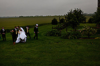 Wellsville, Kansas, May 28, 2011 - A wedding party finishes their portraits  at Fourth generation family farmer Robin Dunn's farm, Dunn's Landing. Dunn has expanded her farm to include agribusiness - using the farm for weddings, school tours, wagon rides, etc... - as a means to bring in extra income. She says diversity if the key to staying in business these days. ..She bought her great grandparents homestead from her father in 1993, and today grows soybeans, corn, sorghum and hay, and maintains a small herd of Black Angus cattle and eight horses which she uses to for wagon and stage coach rides.  According to the most recent Department of Agriculture data, there are more than 306,000 farms run primarily by women in 2007, representing about 14 percent out of the 3.3 million American farms.  That's up from 237,819 or 11 percent in 2002, and a big increase from the 1980s when about five percent of U.S. farms were operated by women.Dunn has branched out from her farming business, using her century-old dairy barn to host 25 to 30 weddings and other events a year. She also attracts tourists for farm tours and carriage rides, and holds sessions with school children to teach them about faming.