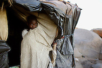A child living in a squatter camp whose residents have constructed huts out of plastic sheeting and other scavenged materials.