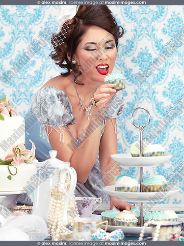 Woman with a beautiful hair style and luxurious dress is tempted to eat a cupcake from a tea party table