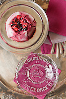 Close up of a summer pudding prepared by chef Maddalena Caruso and served next to a glass plate commemorating the coronation of King George VI