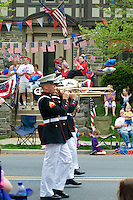 US Marine corps band and spectators  Loyalty day patriotic parade in small town USA.