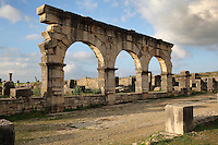 Portico of a large house West of the Palace of Gordian on the Decumanus Maximus, with arches forming the facade of shops, North East quarter, Volubilis, Northern Morocco. The house is built around a small peristyle courtyard with a central pool and shops on both facades, with a secondary apartment with heated rooms to the North East. Volubilis was founded in the 3rd century BC by the Phoenicians and was a Roman settlement from the 1st century AD. Volubilis was a thriving Roman olive growing town until 280 AD and was settled until the 11th century. The buildings were largely destroyed by an earthquake in the 18th century and have since been excavated and partly restored. Volubilis was listed as a UNESCO World Heritage Site in 1997. Picture by Manuel Cohen