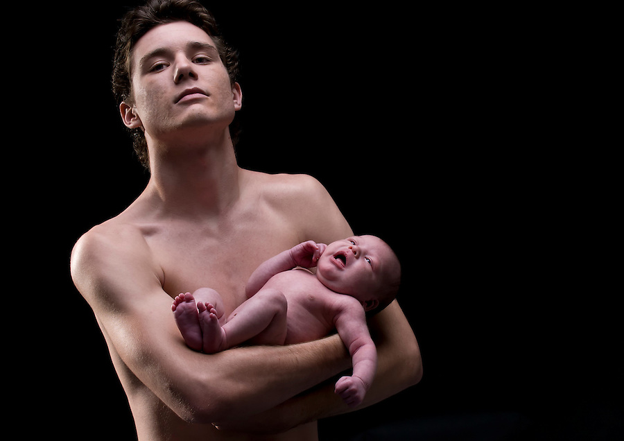 Portrait of very young father holding newborn baby, very proud.