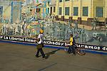 Two Nicaraguan teenagers walk past a Sandinista mural showing a revolutionary battle, Leon, Nicaragua
