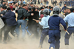 Police with billy clubs and riot helmets charge into a crowd of men waiting to apply for jobs as police officers in Kirkuk, Iraq. Officials sought to fill 1,300 slots for the next training class, but were overwhelmed when more than 4,000 applicants showed up. More than half were turned away, and hundreds of others waited for hours, but never got a chance to submit their papers. The event was shut down after a U.S. advisor observed an Iraqi recruiting officer take a bribe from an applicant. Desperate job seekers were ordered to disperse, but many refused, so police resorted to violence to force them from the grounds. Dec. 6, 2007. DREW BROWN/STARS AND STRIPES