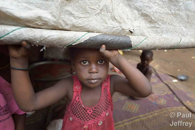 A girl looks out from her shelter in a camp for more than 12,000 internally displaced persons located on the grounds of the Roman Catholic Cathedral of St. Mary in Wau, South Sudan. Most of the families here were displaced in June, 2016, when armed conflict engulfed Wau.<br /> <br /> Norwegian Church Aid, a member of the ACT Alliance, has provided relief supplies to the displaced in Wau, and has supported the South Sudan Council of Churches as it has struggled to mediate the conflict in Wau.
