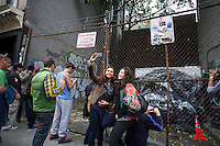 Graffiti enthusiasts flock to a vacant lot in the Lower East Side neighborhood of  New York on Wednesday, October 9, 2013 to see the ninth installment of Banksy's graffiti art. This particular installment is viewed through a chain link fence and a locked fence. The elusive street artist is creating works around the city each day, during the month of October accompanied by a satirical recorded message parodying a museum tour which you can get by calling the number 1-800-656-4271 followed by  # and the number of artwork.  (© Frances M. Roberts)