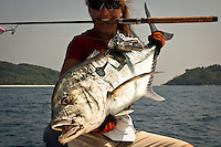 This woman in her late 30s is holding a Giant Trevally, and grabbing the rod with her beautiful white teeth