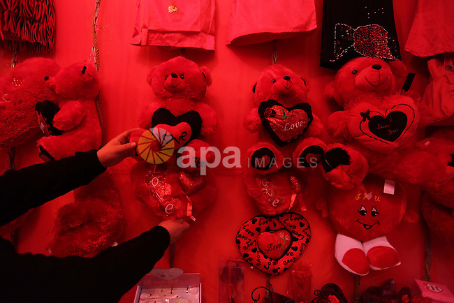 A Palestinian vendor displays gifts at his store ahead of Valentine's day in Gaza City on February 12, 2014. Valentine's Day is increasingly popular among younger Palestinians, many of whom have taken up the custom of giving cards, chocolates and gifts to their sweethearts to celebrate the occasion. Photo by Ashraf Amra