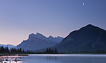 The moon shines above Mount Rundle during a clear, misty morning along the Vermillion Lakes road in the Banff National Park area of Alberta Canada.