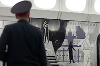 """Moscow, Russia, 20/06/2010..A policeman looks at murals depicting Raskolnikov's double murder and Svidrigailov's suicide in Crime & Punishment at the just-opened Dostoevsky metro station, the newest in Moscow's underground metro system. The station's opening was delayed by several weeks after psychiatrists claimed the gloomy and violent images in murals depicting scenes from Dostoevsky's novels would make the station a """"mecca for suicides""""."""
