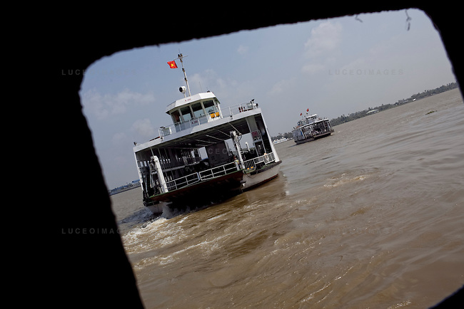 "Passengers cross the Hau Giang River, a tributary of the Mekong River, by ferry in Long Xuyen, the capital of An Giang Province, Vietnam. When the Mekong River reaches Vietnam it splits into two smaller riveres. The ""Tien Giang"", which means ""upper river"" and the ""Hau Giang"", which means ""lower river"". Photo taken on Monday, December 8, 2009. Kevin German / Luceo Images"