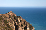 A mountain peak with the Pacific Ocean in the distance in Point Mugu State Park just north of Malibu, California, USA