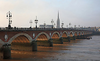 The Pont de Pierre, built 1810-22 under Napoleon I by engineers Claude Deschamps et Jean-Baptiste Basilide Billaudel, over the river Garonne, Bordeaux, Aquitaine, France. The stone and brick bridge links the town centre with the La Bastide district, is 487m long and is constructed on 17 arches held by 16 pillars. It was originally built by 4,000 workers and was widened in 1954. In the distance is the spire of the Basilique Saint Michel or Basilica of St Michael, a Flamboyant Gothic church built 14th - 16th centuries. Picture by Manuel Cohen
