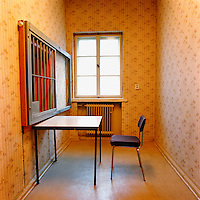 A table and chair sit in front of a grille in the visitors' room in the former Stasi remand prison, Hohenschonhausen.. CHECK with MRM/FNA