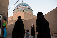 A group of women walking near .the 1323 CE Masjid-e Jame (Friday Mosque).