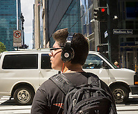 A young adult wearing his Beats headphones in New York on Wednesday, August 12, 2015.  (© Richard B. Levine)