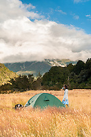 Woman camping on grassy clearing next to Perth River with great mountain views, South Westland, West Coast, New Zealand, NZ
