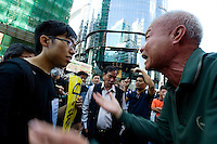 HONG KONG, CHINA - NOVEMBER 25: A pro-democracy protester (left) and a person opposing the blocking of the street by the Occupy Central movement have a heated argument in the Mongkok area in the presence of bailiffs on November 25, 2014 in Hong Kong, Hong Kong Special Administrative Region, China. The Mong Kok protest site is scheduled for clearance by baliffs this week after Hong Kong's high court authorized police to arrest protesters who obstruct bailiffs on the three interim restraining orders. (Photo by Lucas Schifres/Getty Images)