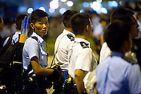 HONG KONG, HONG KONG SAR, CHINA - OCTOBER 02: A police officer with anti-riot gear (left) faces protestors threatening government buildings, as part of a pro-democracy sit-in known as 'Occupy Central', in Tamar square, Admirality, Hong Kong, on October 2, 2014. Also called the 'Umbrella revolution', the Occupy Central civil disobedience movement began in response to China's decision to allow only Beijing-vetted candidates to stand in the city's 2017 election for the top civil position of chief executive. Protest leaders now demand the resignation of Hong Kong's Chief Executive C.Y. Leung Chun-ying. (Photo by Lucas Schifres/Getty Images)
